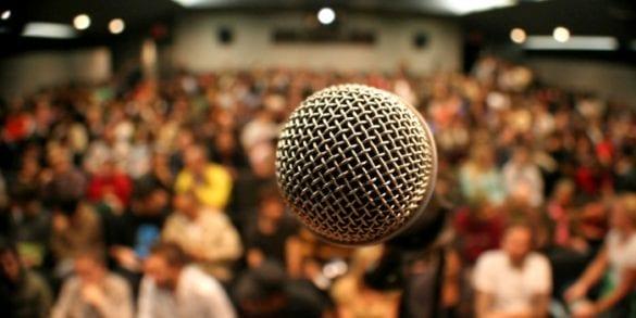 konferencia prednaska mikrofon podium pohlad na ludi publikum closeup blur