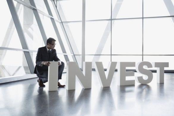 muz drzi napis invest v hale investovanie biznis manager