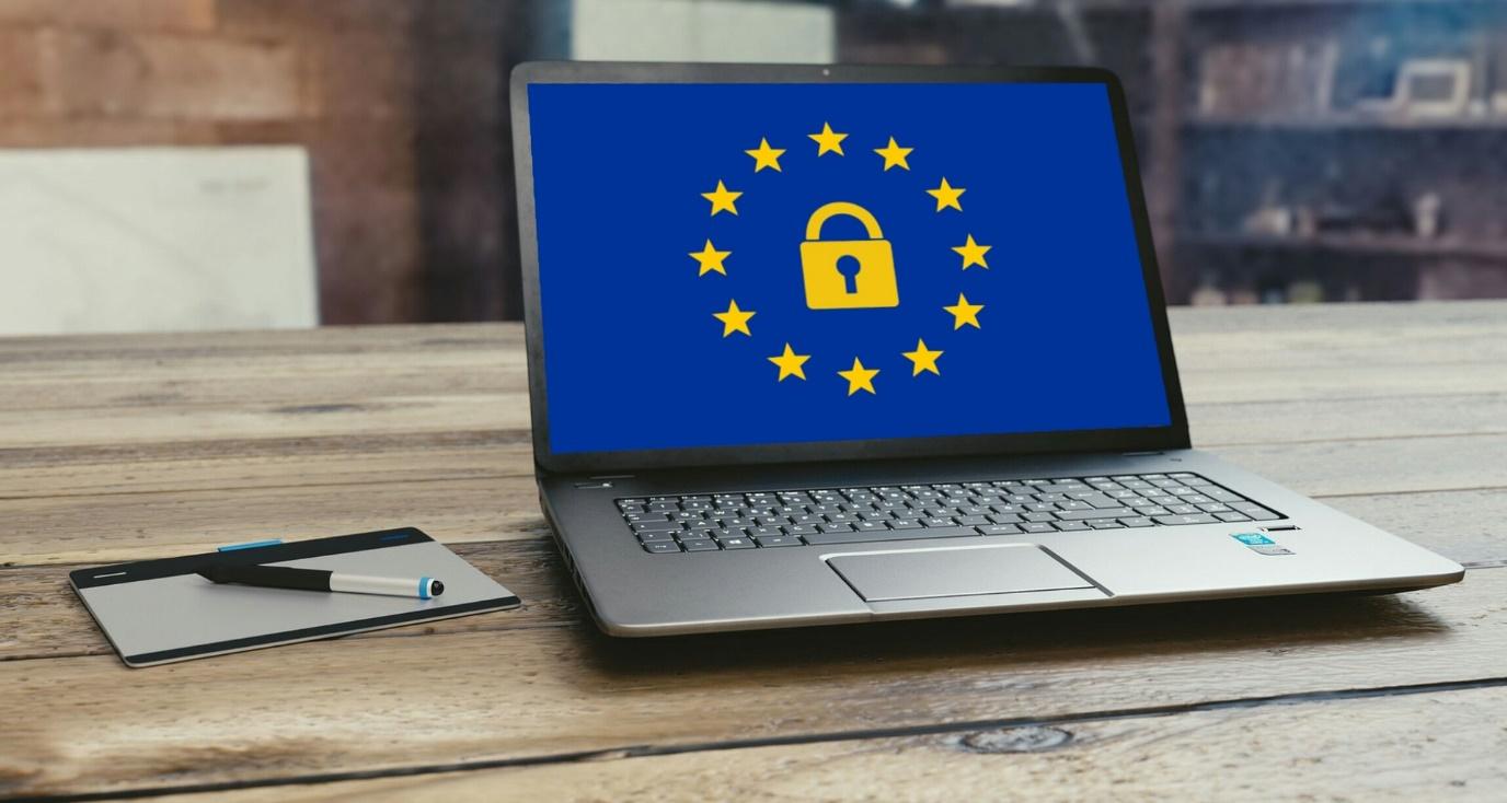 gdpr law zakon ochrana osobnych udajov laptop na drevennom dreve drevo stole stol zapisnik notes pero